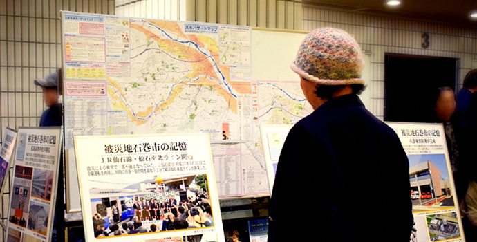 Photo: A woman reads a display explaining the impact of the 2011 Tohoku Earthquake